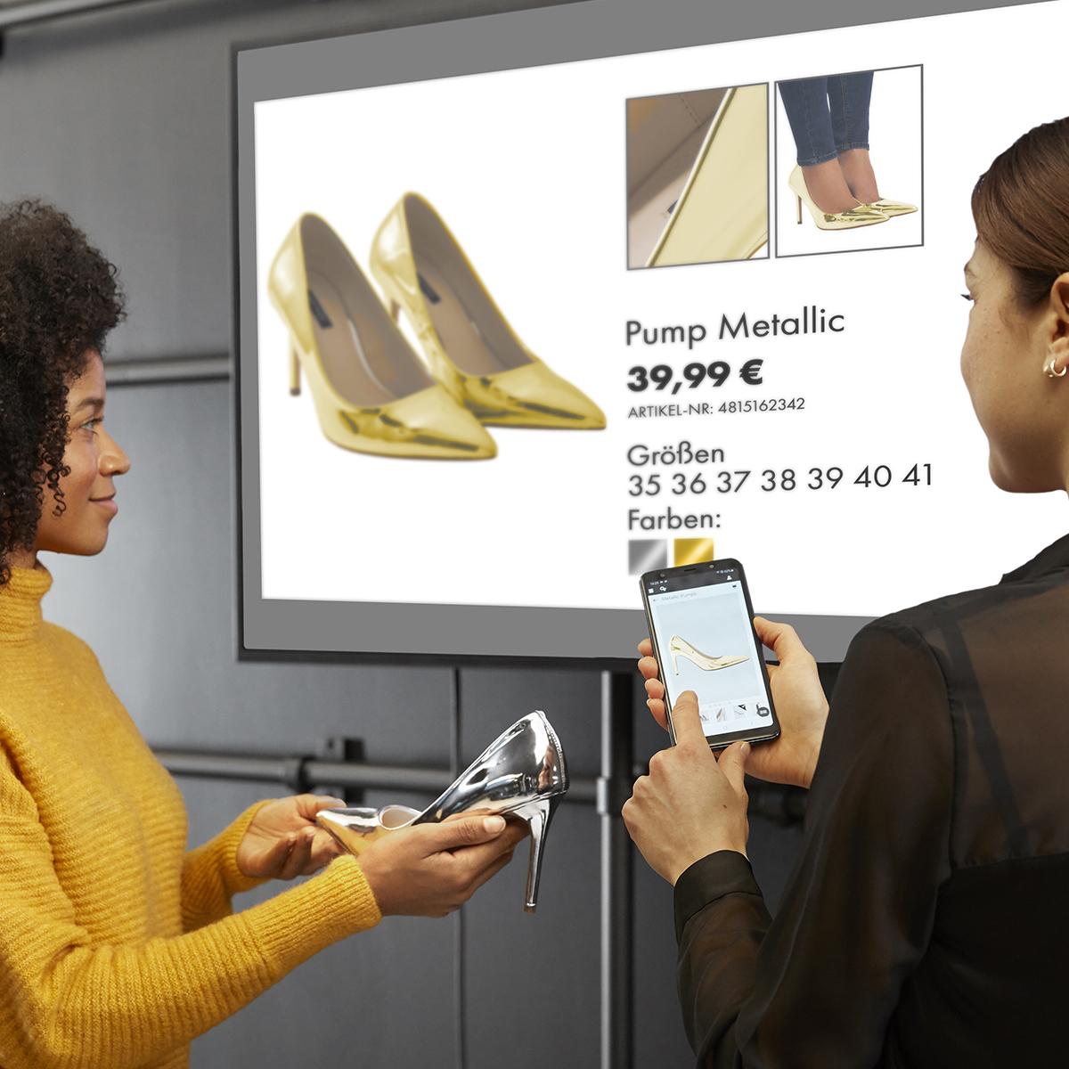 Guided Selling: Verkäuferin zeigt Kundin Details zu ihrem Produkt