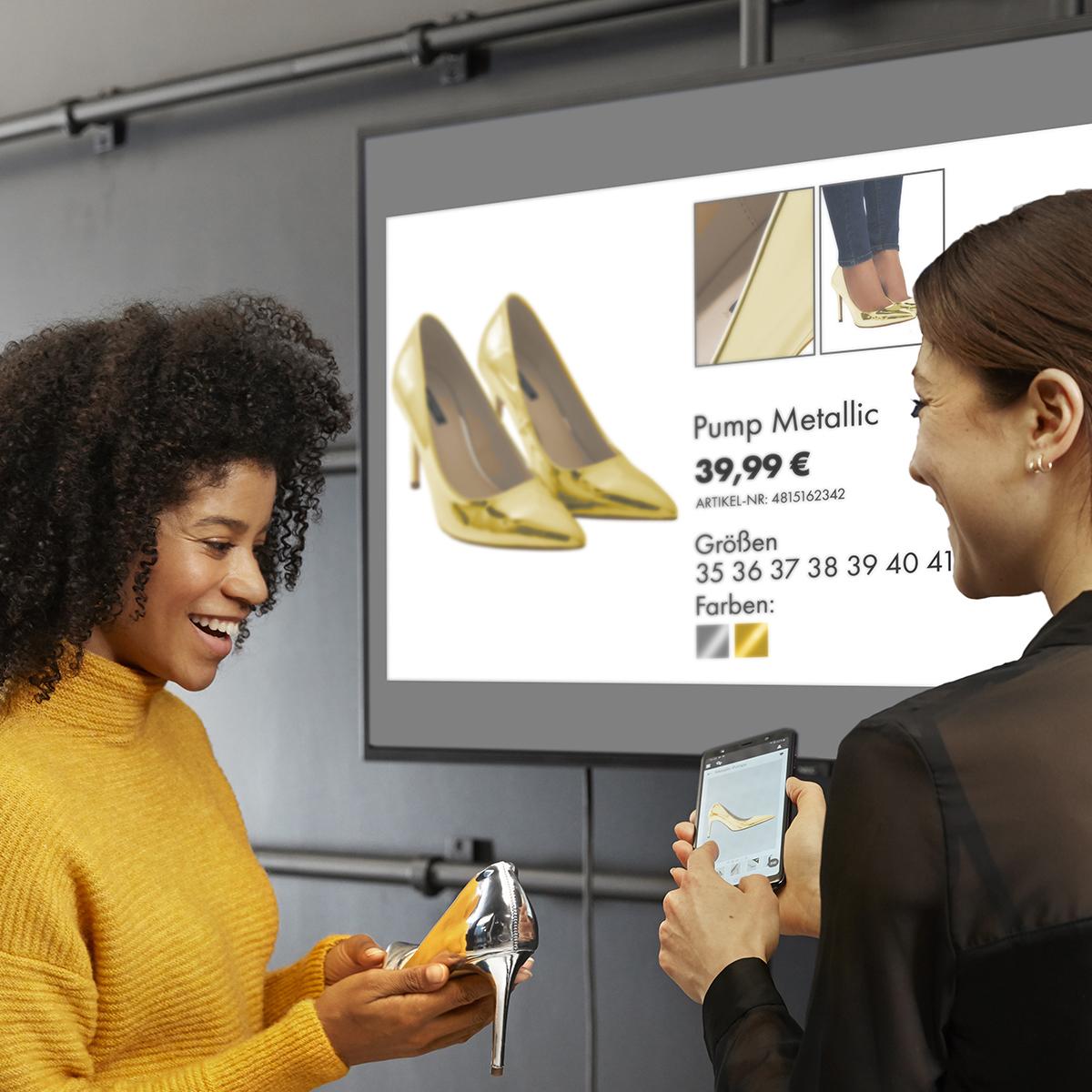 Verkäuferin zeigt Kundin Informationen zu ihrem Produkt auf dem InStore Assistant un einem Digital Signage Bildschirm