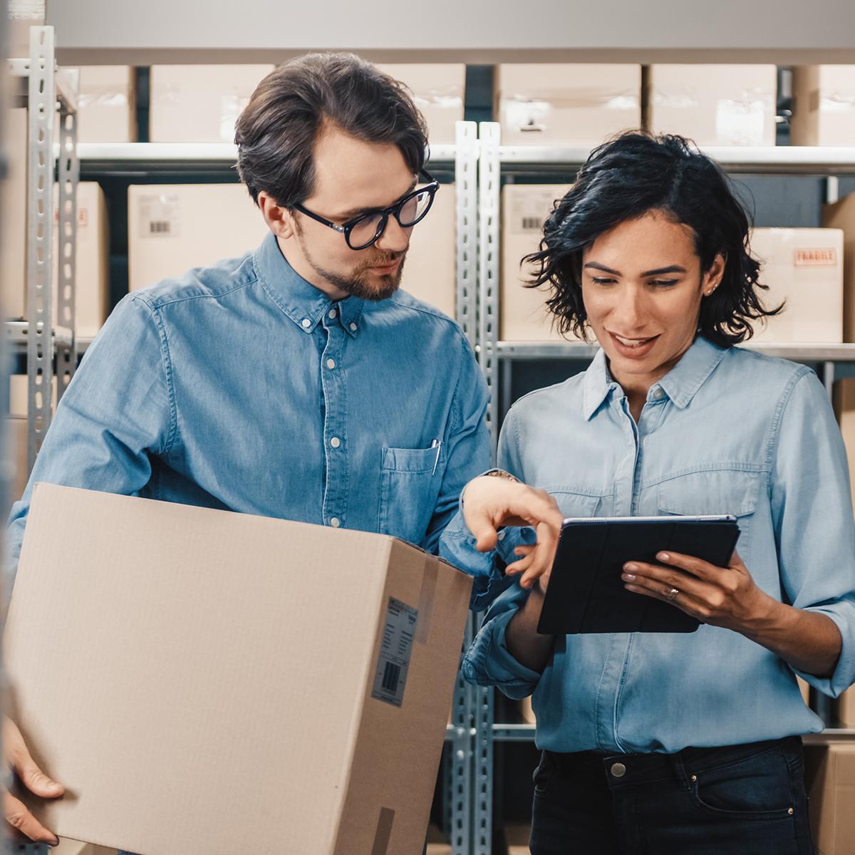 Inventur: Ein Mann und eine Frau, die etwas auf einem Tablet ansehen, der Mann hält einen Karton in der Hand.