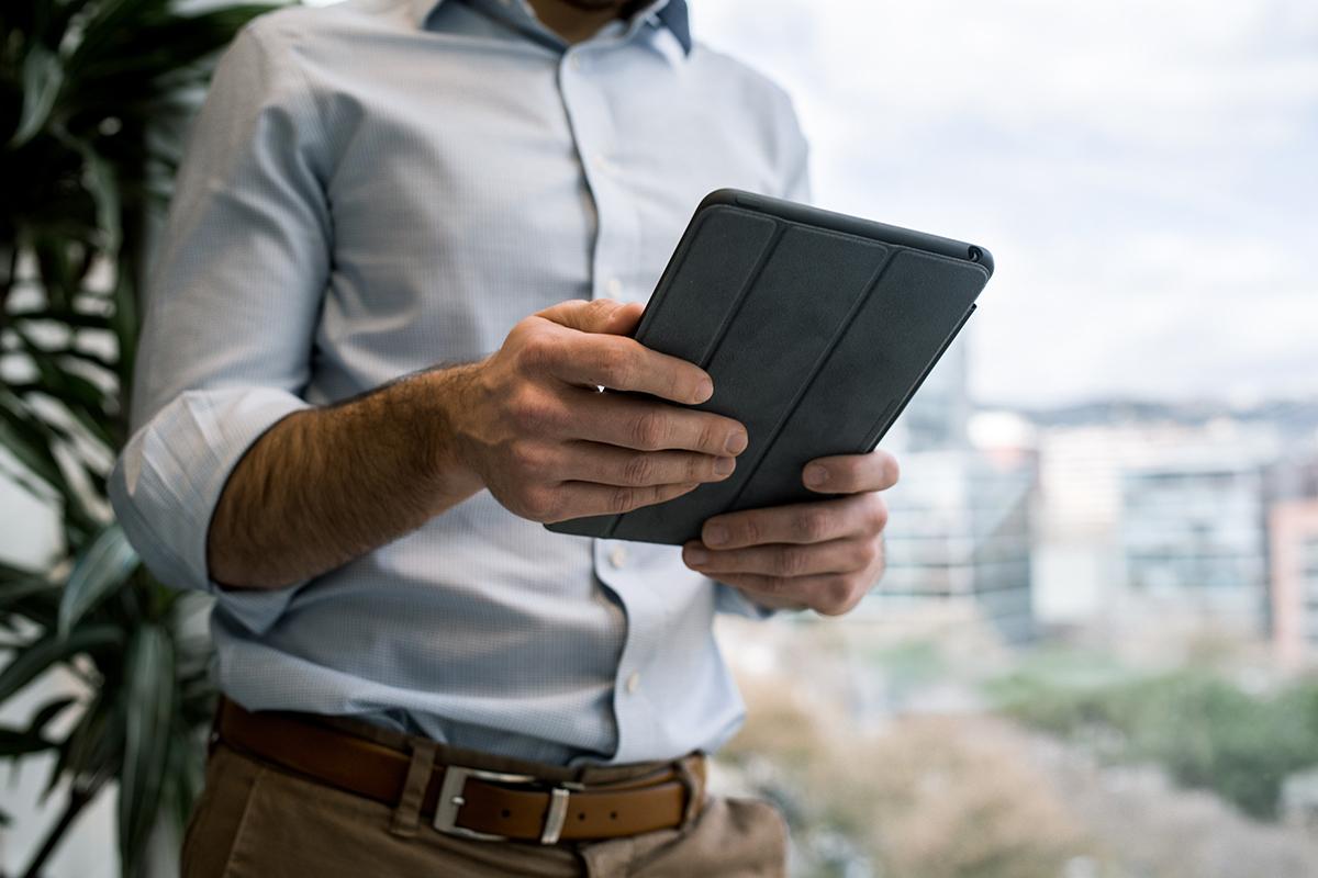 Mann hält Tablet in der Hand