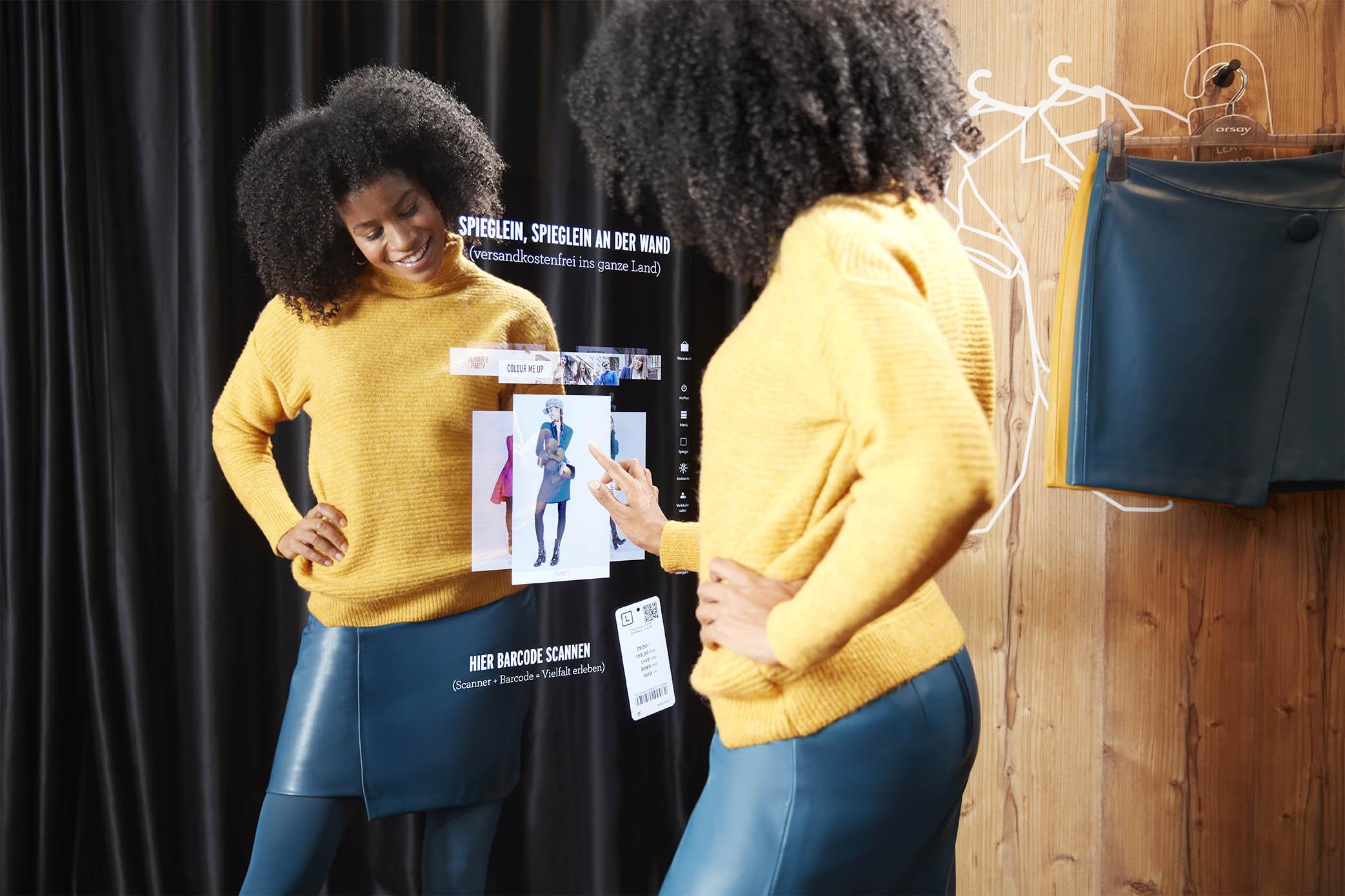 Kundin sieht sich Details eines Outfits im Spiegel des Interactive Fitting Rooms an