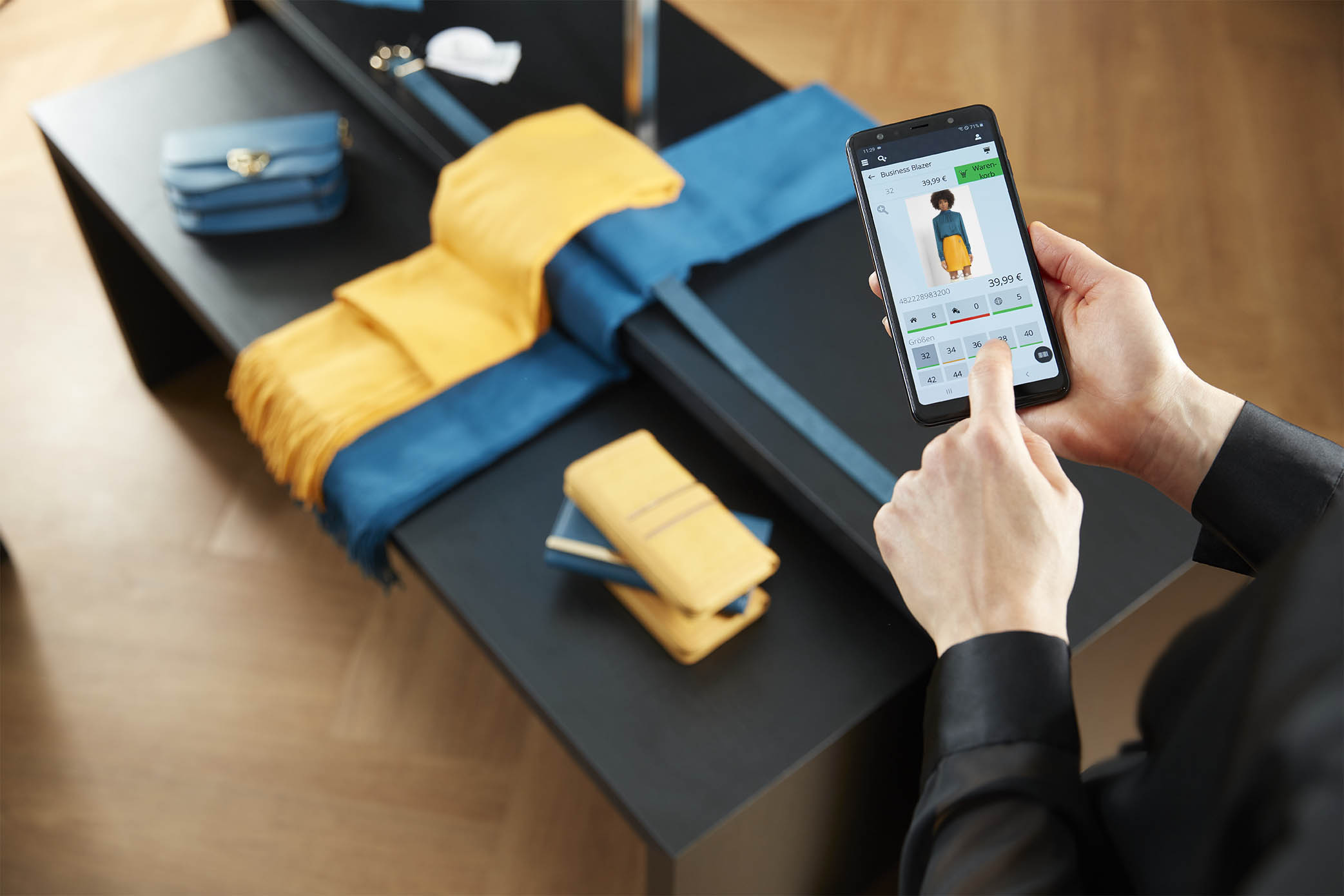 Detailansicht des InStore Assistants: Verkäuferin sieht in der Handy-App ein Outfit an und prüft die Bestände