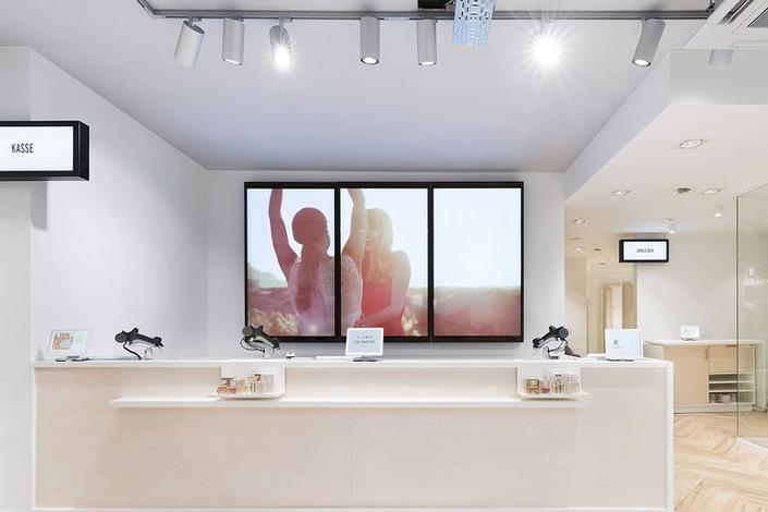 Digital Signage Bildschirme hinter der Kasse bei Orsay