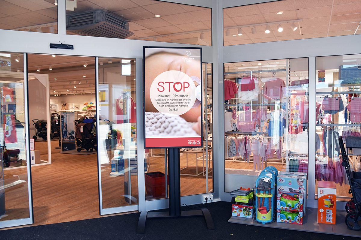 Digital Signage LCD Screen mit angebundenem Sensor zum Zählen von Kunden vor dem Eingang einer BabyOne Filiale