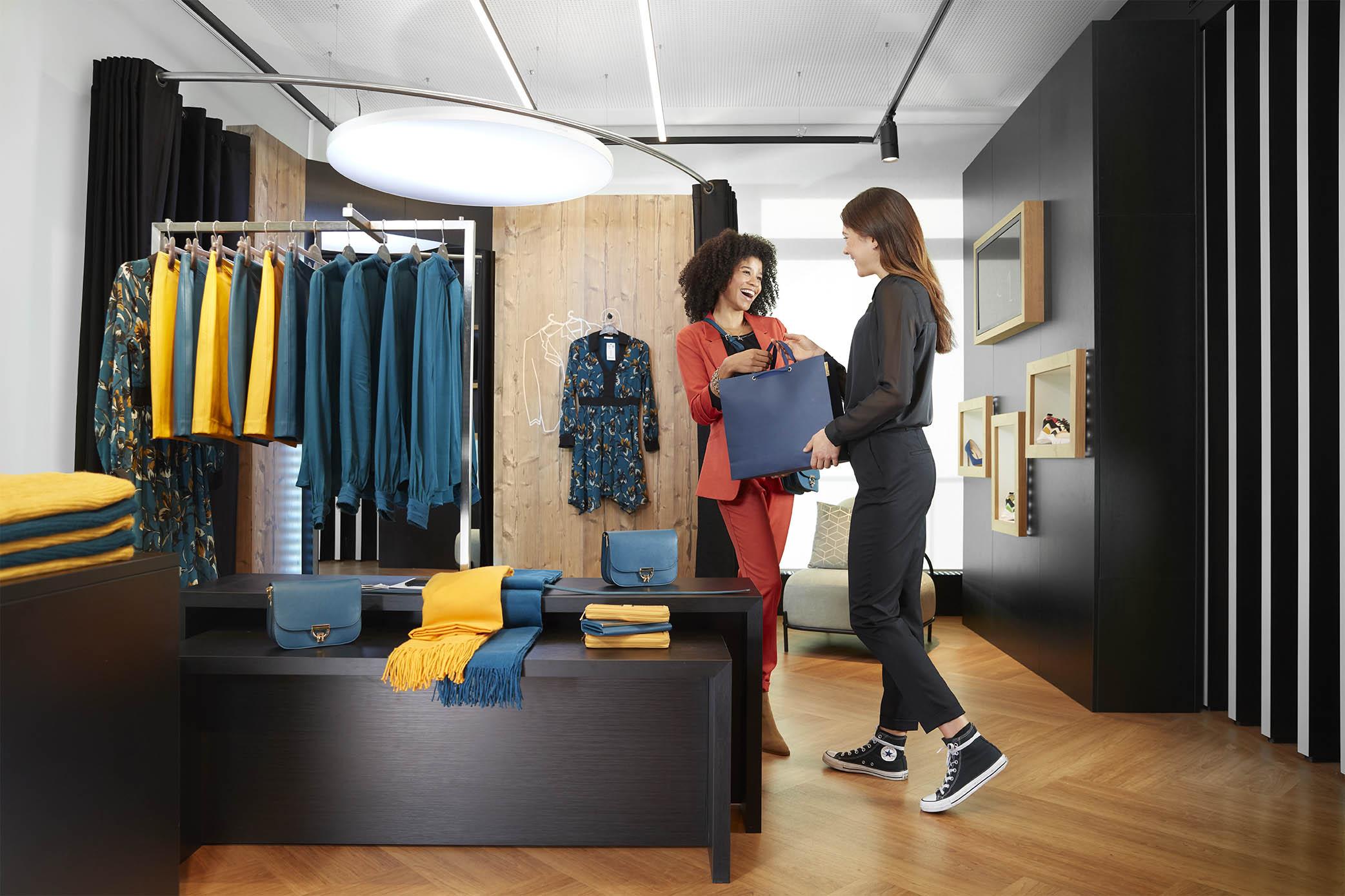 Verkäuferin übergibt Kundin eine Tasche mit ihren Omnichannel-Einkäufen
