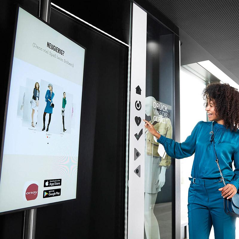 Interaktives Schaufenster: Eine junge Frau bedient Touch-Buttons